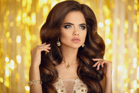 Beauty fashion woman in gold. Elegant brunette with makeup, long wavy hair style, pendant golden jewelry set, manicured nails. Fashionable glamour girl model in luxury over bokeh lights background.