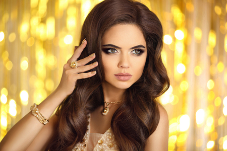Beautiful fashion woman in gold. Elegant brunette with makeup, long wavy hair style, pendant golden jewelry set, manicured nails. Fashionable glamour girl model in luxury over bokeh lights background. Stock Photo