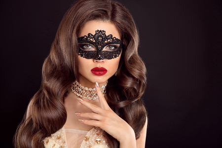 Beautiful wavy hair. Beauty Glamour Woman with luxurious long healthy brown hair wearing lace mask. Red lips makeup. Fashion golden diamond jewelry. Elegant lady isolated on black background.