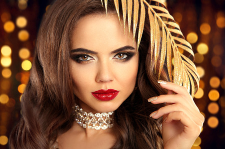 Beauty fashion brunette portrait in gold. Sexy elegant woman with red lips, golden eyeshadow makeup with manicured nails in expensive diamond necklace over party lights background.