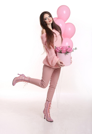 Pretty young woman in pink holding rose flowers in hat box over balloons isolated on white background. Happy brunette having fun. Stock Photo