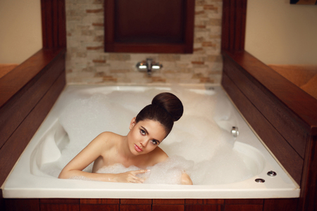 Young woman relaxing in foam jacuzzi bath spa, brunette enjoying the aromatherapy in wellness center. Beautiful model in luxury spa resort. Beauty skin care treatment.