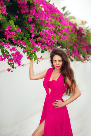 Fashion outdoor photo of gorgeous sensual woman in pink swimsuit dress over bougainvillaea flowers blossom branch on luxury resort villa in Santorini, Greece