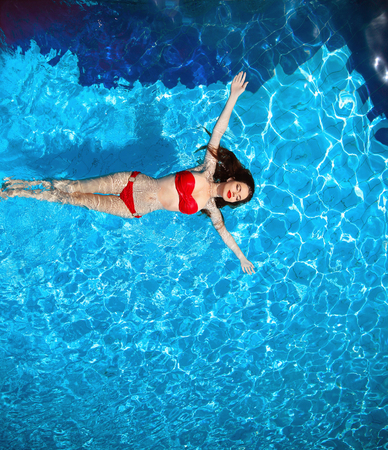 Top view of Fashion sexy bikini tanned model in blue water swimming pool on luxury resort. Beautiful brunette woman enjoying life at summer holiday on the beach.