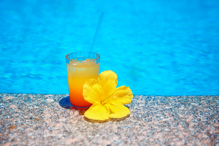 Cocktail with yellow flower over blue surface water background. Exotic vacation. Tropical drink. Stock Photo