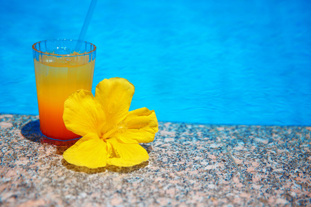 Colourful Cocktail with yellow flower over blue surface water background. Exotic vacation. Tropical drink.