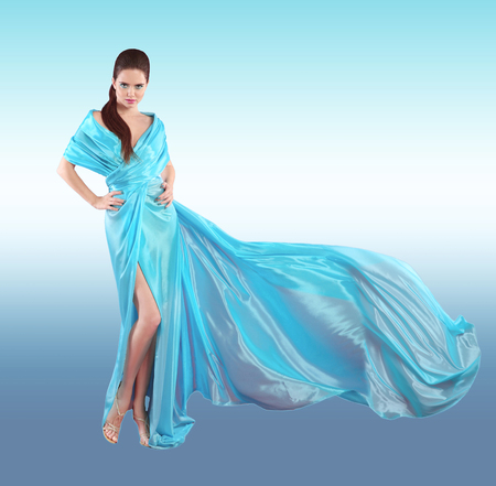 Beautiful fashionable Girl in blowing blue dress. Woman in Flying Gown, Silk Fabric Waving on Wind isolated on studio background.