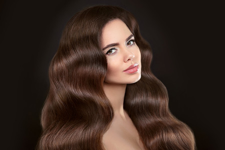Healthy Hair. Beautiful model girl with shiny brown wavy long hairstyle and makeup isolated on black background. Glossy natural hair. Care and hair products. Stock Photo