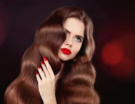 Healthy hair. Red lips & manicure. Wavy hair. Beautiful model girl portrait with shiny brown straight long hairstyle and makeup isolated on black background. Elegant woman.