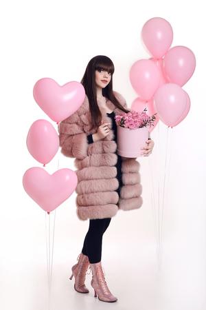 79450672 - Foto de moda de la mujer de moda en el abrigo de piel de color  rosa con rosa ramo de flores en la caja de sombrero sobre globos aislados  sobre ... 270fa81c4eb