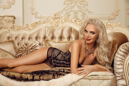Beautiful alluring blond woman in sexy lingerie lying on royal sofa in luxury modern interior. Beauty glamour fashion style photo portrait. photo