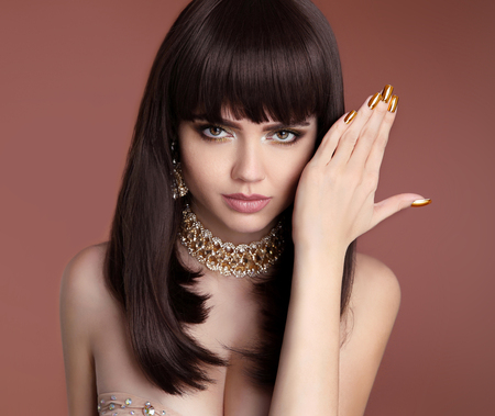Beauty Vogue Hairstyle. Glamour girl closeup. Golden manicured nails. Fashion woman portrait. Sensual lips makeup. Elegant lady with diamond jewelry isolated on studio brown background. Stock Photo