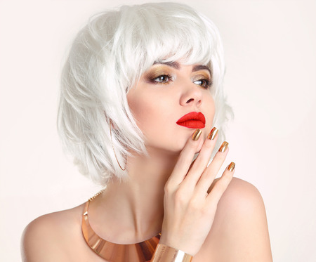 Blonde bob hairstyle. Blond hair. Fashion Beauty Girl portrait. Red lips. Manicured nails and Make-up. Jewelry set. Vogue Style Woman isolated on white background. photo