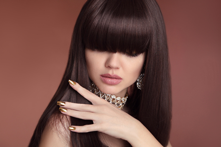 Beauty hair. Vogue Hairstyle. Fashion Manicure. Portrait of gorgeous young dark-haired woman. Sensual lips makeup. Golden polish manicured nails.