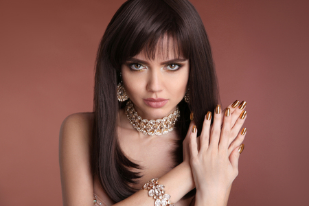 Nails manicure. Beauty girl brunette portrait. Fashion golden jewelry women set. Sexy female with healthy brown hair style, provocative make up and expressive eyes looking straight photo