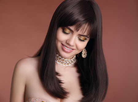 Makeup. Hairstyle. Beauty smiling girl brunette portrait. Fashion golden jewelry women set. Sexy female with healthy brown hair style isolated on studio background. photo