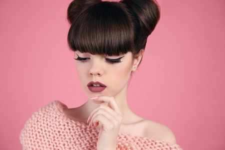 Beauty makeup. Fashion teen girl model. Brunette with matte lips and hairstyle posing over studio pink background.