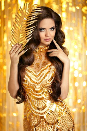 Elegant brunette in golden sparkling dress. Fashion Glamour style. Beauty makeup and wavy hairstyle. Beautiful smiling woman with long hair style posing over gold bokeh lights background.