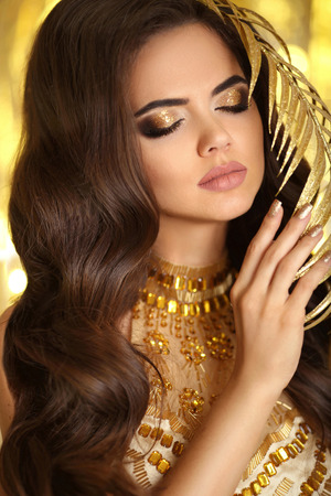 Golden makeup. Elegant brunette woman. Fashion jewelry. Wavy hair style. Matte lips. Sexy lady model in golden dress with gold accessories over bokeh lights party background.