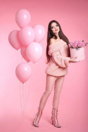 balloon bouquet: Pretty cute brunette girl with balloons holding bouquet of rose flowers in hat box isolated on pink studio background. 8 march. Birthday party.