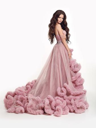 Mooie dame in luxe weelderige roze jurk. Manier donkerbruine vrouw in het schitterende lange toga stellen geïsoleerd op witte studioachtergrond. Stockfoto