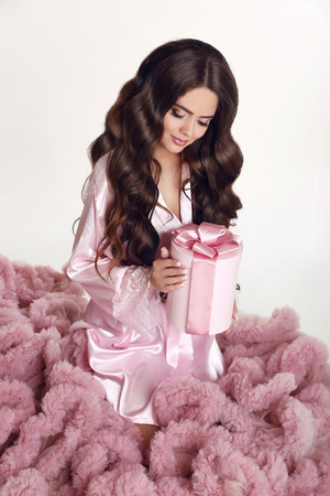 french manicure sexy woman: Beauty wavy hair. Pretty brunette girl portrait. Long wavy hairstyle. Makeup. Attractive young woman holding hat box with pink bow. Gift.