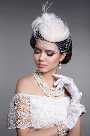 Retro woman portrait. Elegant brunette lady with hairstyle, pearls jewelry set wears in hat and lace gloves posing over studio grey background.