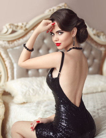 Elegant brunette sexy woman in fashionable black dress. Attractive girl model with red lips hollywood makeup, retro wavy hair style and fashion gems jewelry set Stock Photo