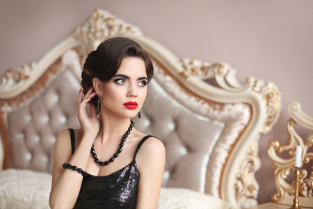 Elegant brunette sexy woman in fashionable black dress. Fashionable glamour model with red lips hollywood makeup, retro wavy hair style and fashion gems jewelry set