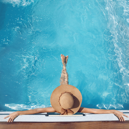 Top view of woman in straw hat relaxing in swimming pool at luxury villa resort. Summer holiday idyllic background. Vacations Concept. Exotic Paradise. Stock Photo