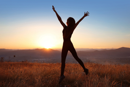 Sunset. Free woman silhouette jumping enjoying outdoors in a wheat field.