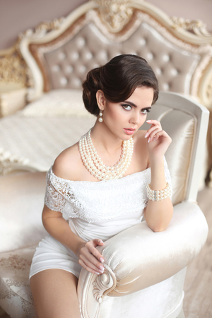 Retro woman portrait. Elegant brunette lady with fashion pearls jewelry set, wavy hairstyle and makeup. Gorgeous model posing on luxury armchair in modern interior.