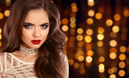 Glamour fashion brunette girl portrait. Long wavy hair style. Red lips beauty Makeup. Sexy model in sequin dress over golden bokeh lights background. Stock Photo