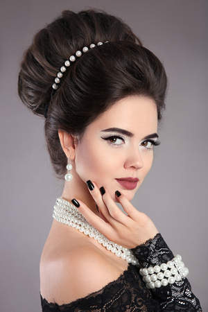 Elegant fashion jewelry woman portrait. Brunette lady with makeup and hairstyle, pearls accessories set posing isolated on studio background. Black polish Manicured nails.