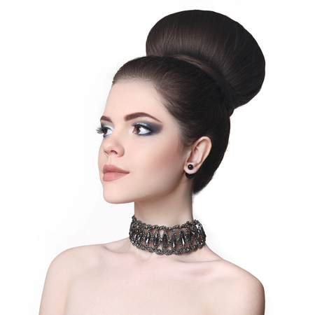 Beauty makeup girl. Fashion bun hairstyle. Attractive teen brunette with choker isolated on studio white background. Imagens