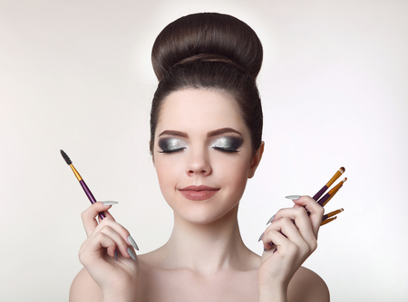 Makeup artist. Pretty teen girl with cute bun hairstyle and fashion beauty makeup, brunette holding brushes in hand isolated on white studio background. Stock Photo