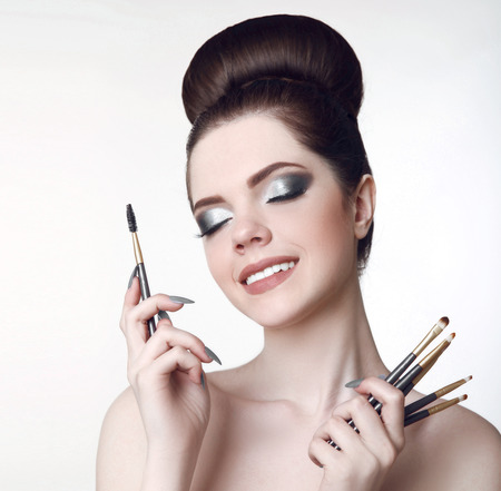 nails: Makeup artist. Pretty teen girl with cute bun hairstyle and fashion beauty makeup, brunette holding brushes in hand isolated on white studio background. Stock Photo