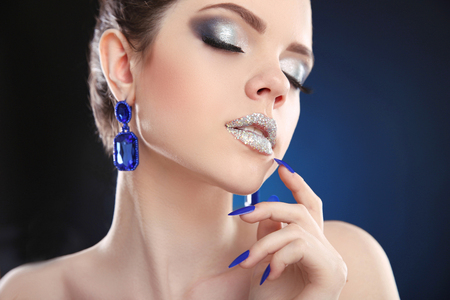 nails: Lips. Sparkle Makeup. Closeup of beauty fashion girl with silver lipstick and glitter eyeshadow, wears in blue earrings jewelry over dark studio background.