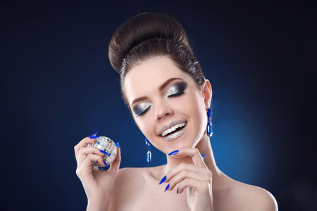 nails: Beauty Fashion makeup and manicure nails. Smiling girl with cute bun hairstyles holding disco ball on party light dark background. Stock Photo