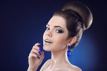 Pretty teen girl with cute bun hairstyles, beauty fashion glitter makeup and blue manicured nails, gems earring jewelry posing on studio background. Stock Photo