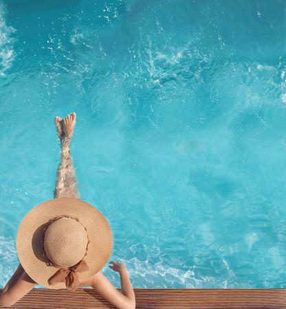 Hintere Ansicht der Frau im Strohhut, der im Türkiswasserswimmingpool am Luxuslandhauserholungsort sich entspannt. Sommerferienidyllischer Hintergrund. Ferien-Konzept. Exotisches Paradies.