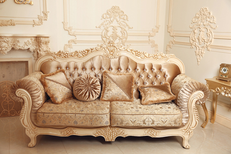 sumptuous: Royal sofa with pillows in beige luxurious interior with ornament frame wall