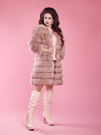 Fashion woman look. Brunette lady in fur coat and leather high boots, lady portrait over pink studio background. Fashionable beautiful brunette model in winter style.  Stock Photo