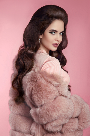 Brunette Woman in fur coat over pink. fashion studio photo of gorgeous sensual woman with long wavy hair in luxurious clothes Stock Photo