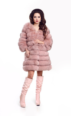 leather texture: Fashion lady in pink fur coat and leather high boots, beautiful brunette model in winter style isolated on studio white background. Fashionable vogue photo.