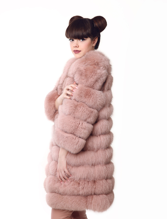 Fashion studio teen look style in pink fur coat isolated on white background. Fashionable young girl with bun hairstyle.