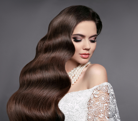Hair Beauty. Elegant bride with Wavy hairstyle. Attractive Sexy Woman With Healthy Long Shiny Brown Hair Posing In Studio. High Resolution.