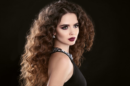 Hairstyle. Fashion brunette girl with Long curly hair, beauty makeup. Glamour portrait of beautiful woman with marsala matte lips isolated on black background. Stock Photo
