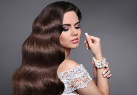 Long healthy wavy hair. Beautiful hairstyle. Beauty makeup. Brunette girl model with shiny curly hair style. Fashion pearl jewelry. Manicured nails. Stock Photo