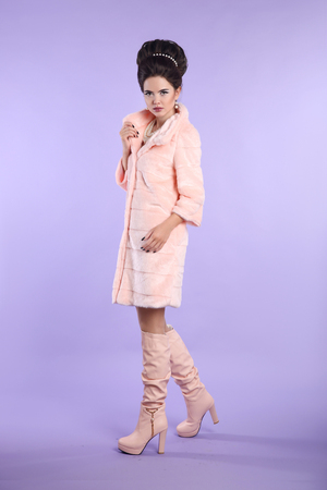 Fashion glamour lady, fashionable woman in pink coat with elegant hairstyle in trendy leather high boots posing isolated on purple studio background.